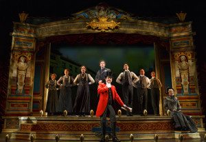 """The cast with Bryce Pinkham as Monty Navarro (standing center), Jefferson Mays as Lord Adalbert D'Ysquith (red), and Jane Carr as Miss Shingle (seated) in a scene from """"A Gentleman's Guide to Love and Murder"""" at the Walter Kerr Theater. Photo credit: Joan Marcus."""